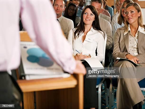 Businesswomen sitting in front row of seminar