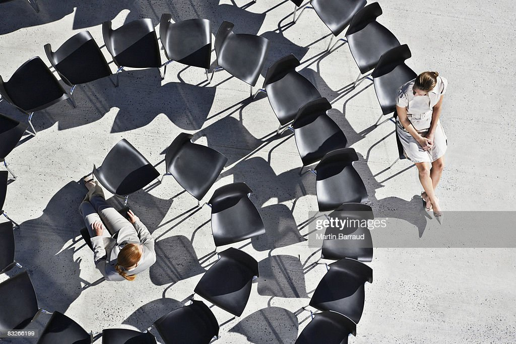 Businesswomen sitting in spiral of office chairs : Stock Photo