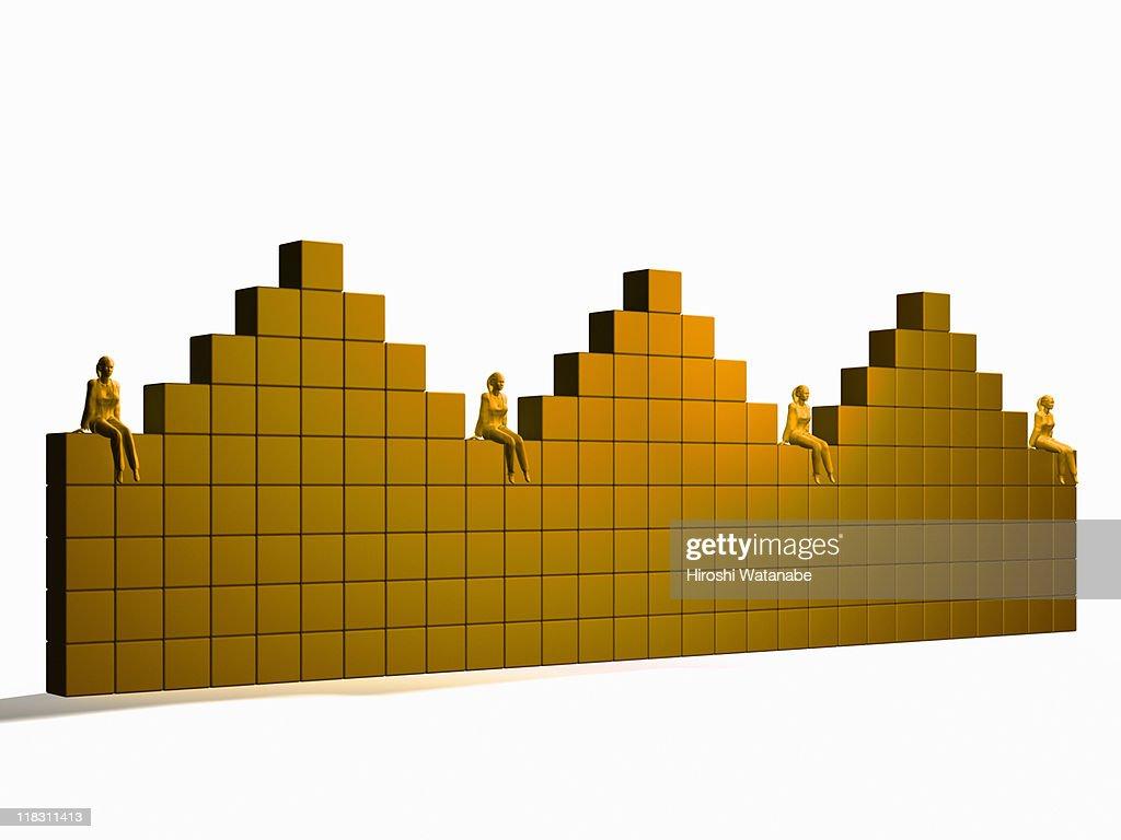 Businesswomen sitting on bar graph : Stock Photo