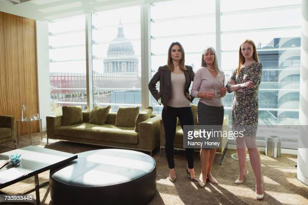 Businesswomen standing by office sofa, London, UK