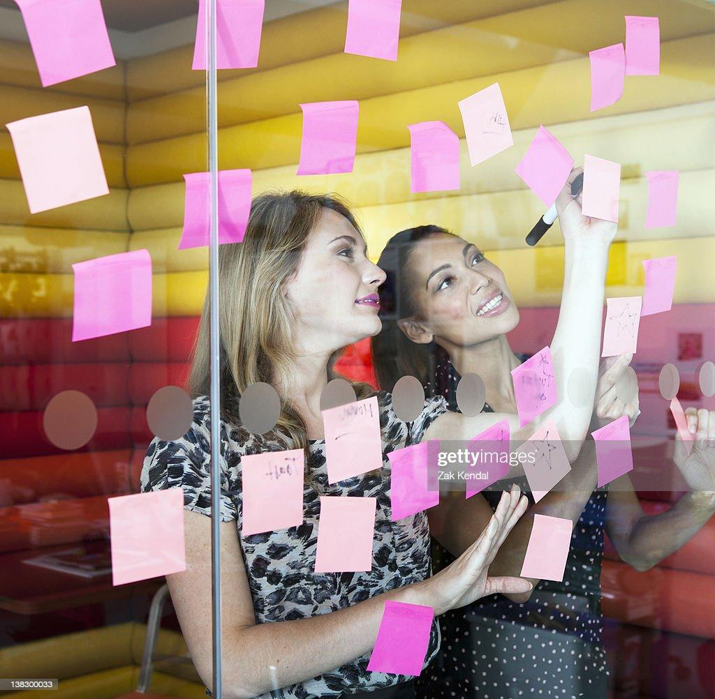 Businesswomen sticking notes on window : Stock Photo