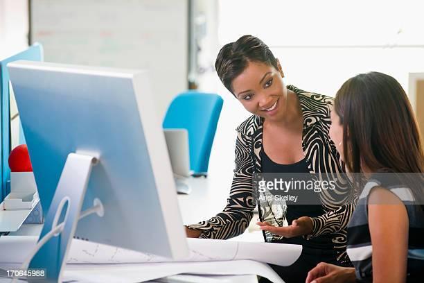 Businesswomen talking at desk