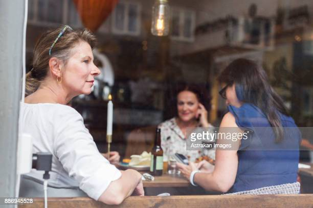 Businesswomen talking during lunch in restaurant, one woman looking through window