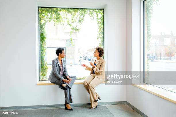 Businesswomen talking in window of office lobby