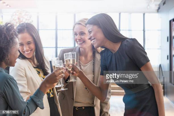 Businesswomen toasting with champagne in office