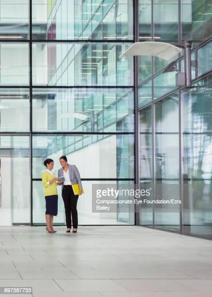 Businesswomen using digital tablet in modern lobby