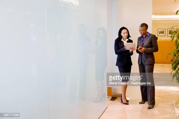 Businesswomen using digital tablet in office corridor