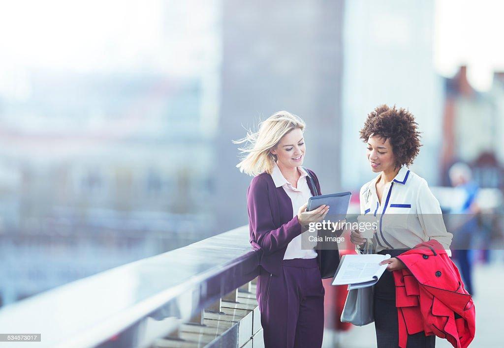 Businesswomen using digital tablet on urban bridge