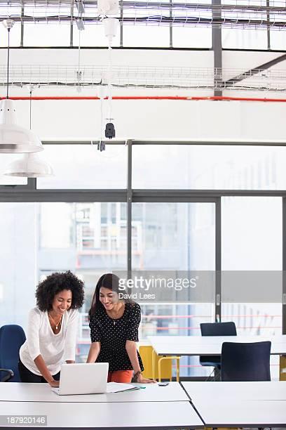 Businesswomen using laptop in modern office
