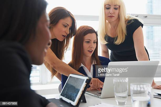 Businesswomen using laptop in office meeting