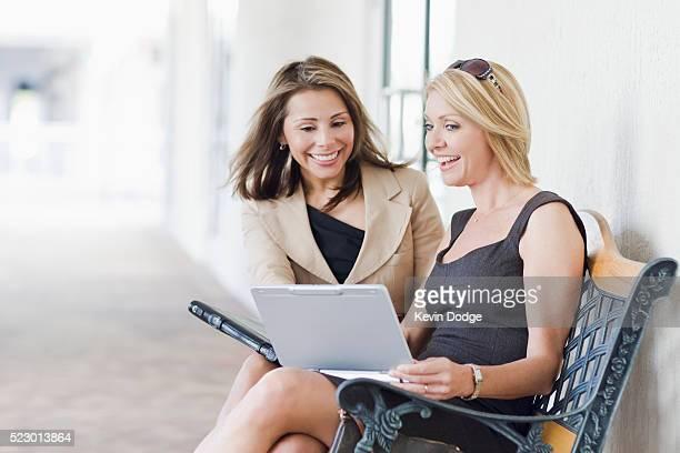 Businesswomen using netbook outside