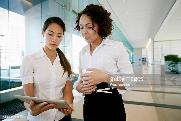 Businesswomen using tablet computer in lobby
