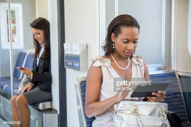 Businesswomen using technology on train