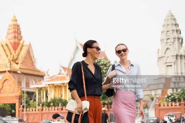 Businesswomen walking by ornate temple, Phnom Penh, Cambodia
