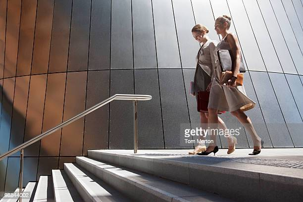 Businesswomen walking down steps outdoors