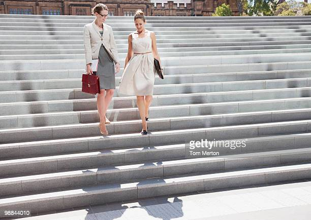 Businesswomen walking down steps outdoors