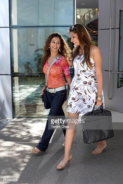 Businesswomen walking in front of office entrance
