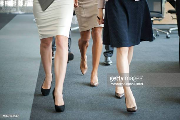 Businesswomen walking in office, low section