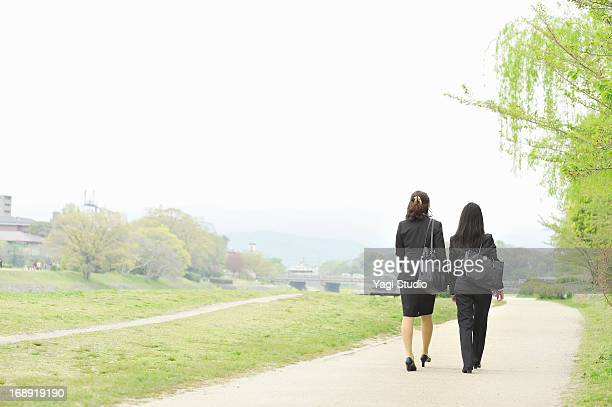 Businesswomen walking the riverbed