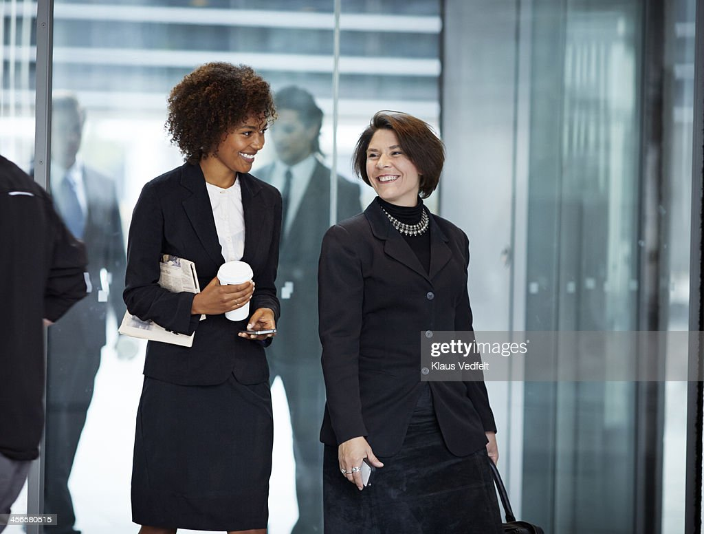 Businesswomen walking threw swing door : Stock Photo