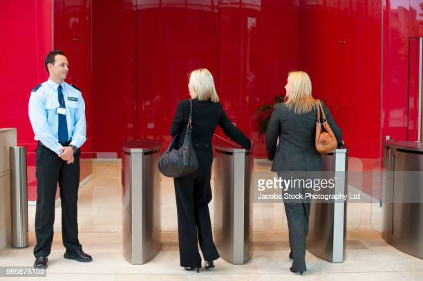 Businesswomen walking through turnstiles near security guard