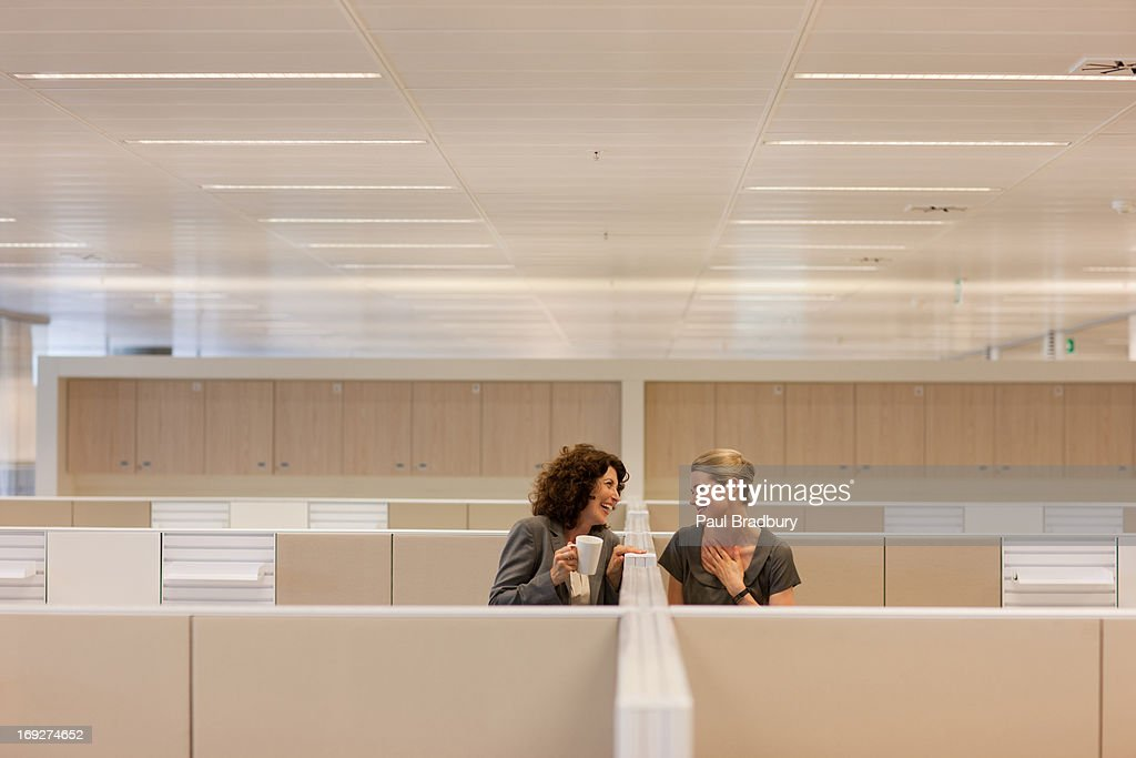 Businesswomen with coffee gossiping in office cubicles