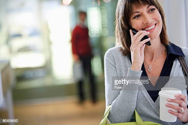 Businesswomen with Coffee Using Cell Phone