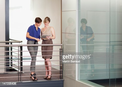 Businesswomen with digital tablet on elevated walkway in office : Stock Photo