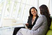 Businesswomen With Digital Tablet Sitting In Modern Office