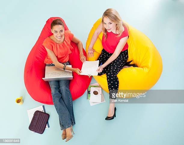 Businesswomen working in bean bag chairs