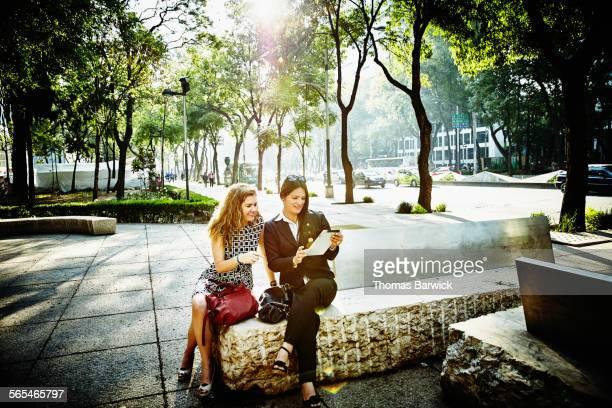 Businesswomen working on digital tablet in park