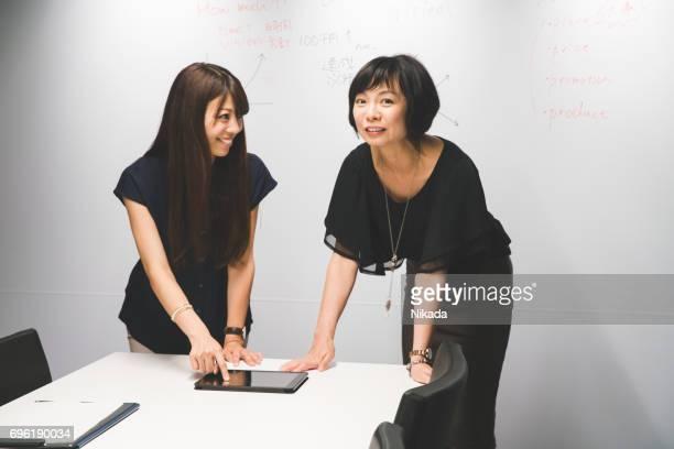Geschäftsfrauen, die auf digitale tablet