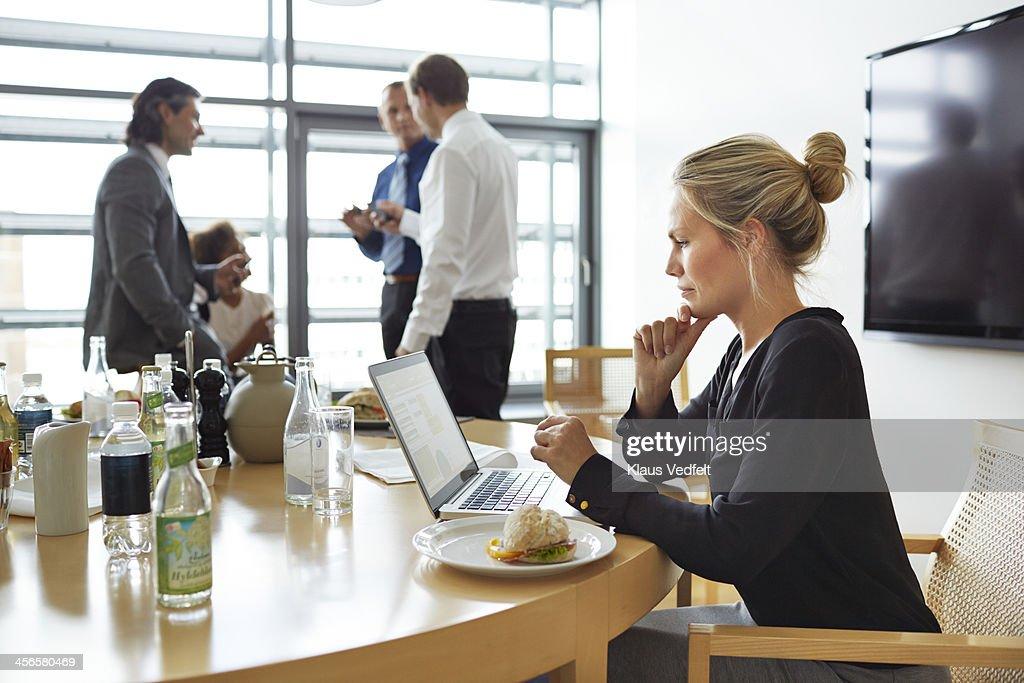 Busineswoman w. laptop, having 'working lunch' : Stock Photo