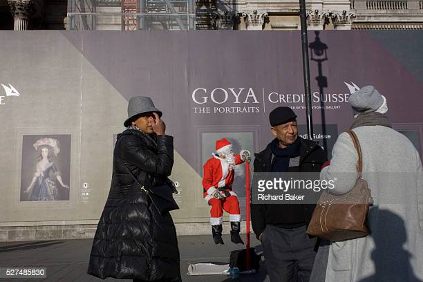 A busker dressed as Santa with visitors to Trafalgar Square central London Seemingly sitting in the frame of a portrait by the Spanish artist Goya we...