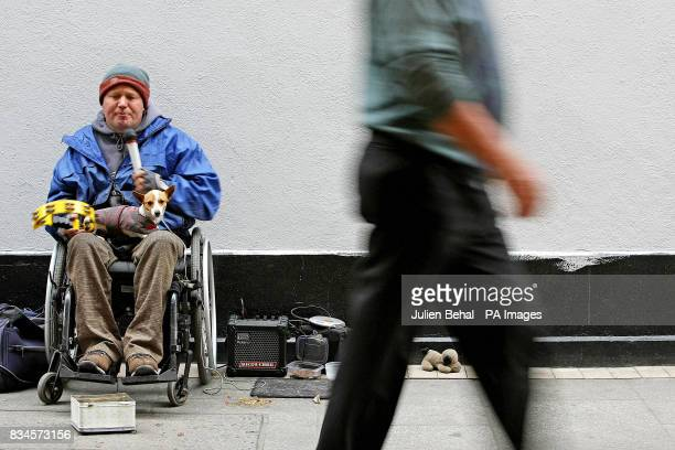 Busker Pat Doyle from Tipperary who lost use of his lower half in a car crash in 1992 busks with his faithful companion Mousey on his lap off Grafton...