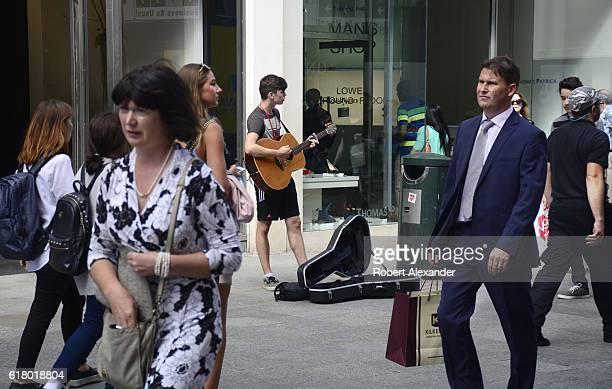A busker performs along pedestrianfriendly Grafton Street in Dublin Ireland