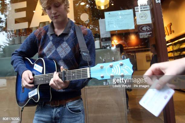 Busker Peter Buffery outside EAT in Soho Square London with his specially designed guitar accepting contactless card payments