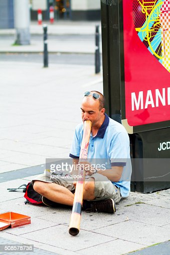 Busker playing didgeridoo : Stock Photo