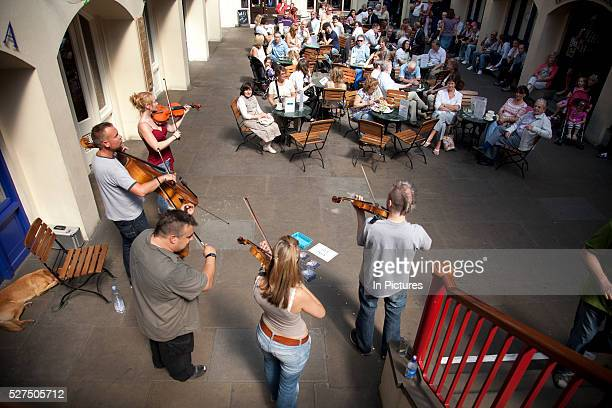 Busking classical musicians play fort an audience of onlookers at Covent Garden Central London The band play opera with a humorous twist in their...