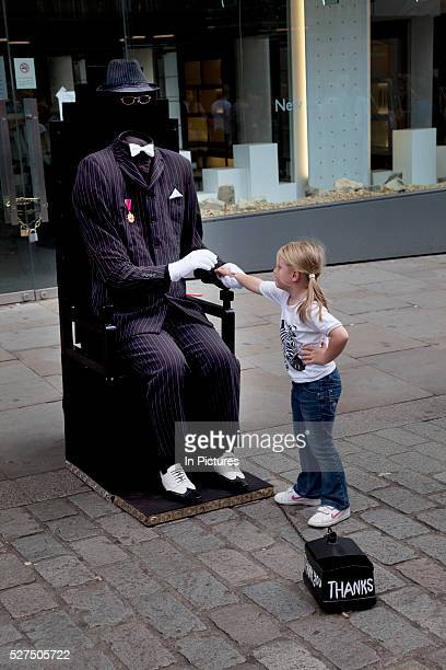 Busking invisible man accepts money from a little girl at Covent Garden Central London In this area there mime style street performers gather