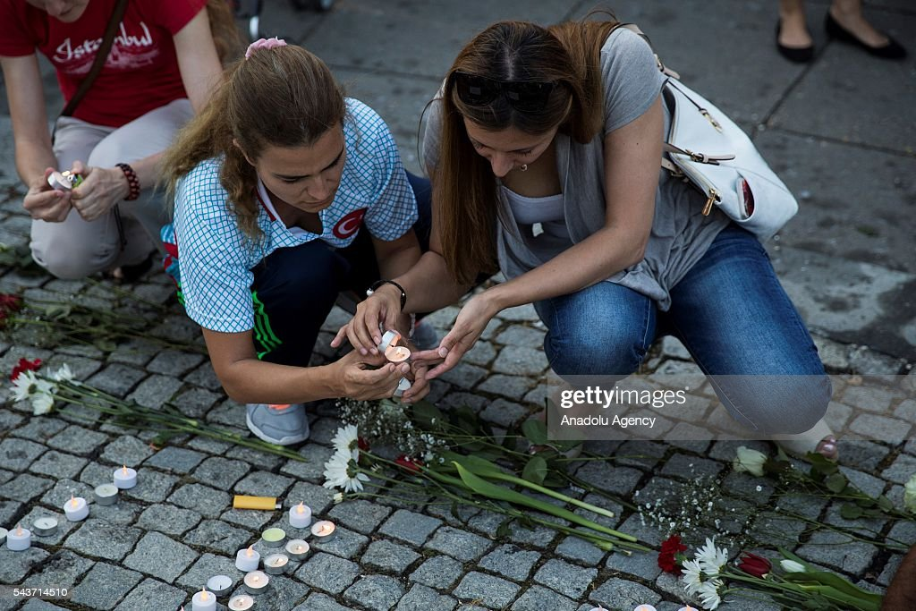 Busra Kayi Tarhan (L) and Burcu Yuksel, both from Istanbul, light candles in Dupont Circle during a vigil for the victims of the Istanbul Airport terrorist attack Washington, USA on June 29, 2016.