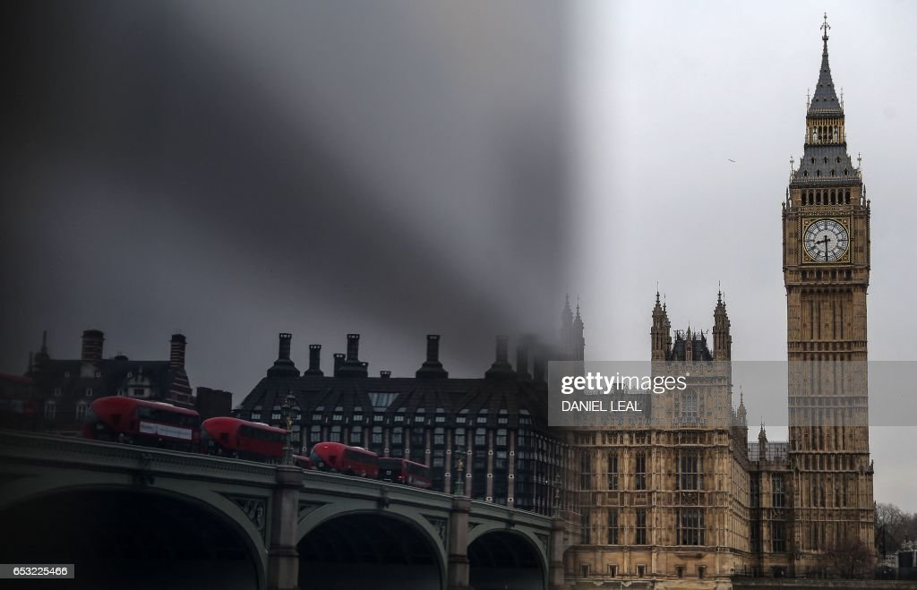 Busses are reflected as they cross Westminster Bridge near The Elizabeth Tower, better known as 'Big Ben', and the Houses of Parliament in central London on March 14, 2017. Prime Minister Theresa May is set to begin the countdown to Brexit after parliament gave her the green light -- and Scotland wrong-footed her by launching a fresh bid for independence. Downing Street has played down speculation that May could announce Tuesday that she is triggering the Article 50 process to leave the European Union, indicating that it would take place later in the month. / AFP PHOTO / Daniel LEAL