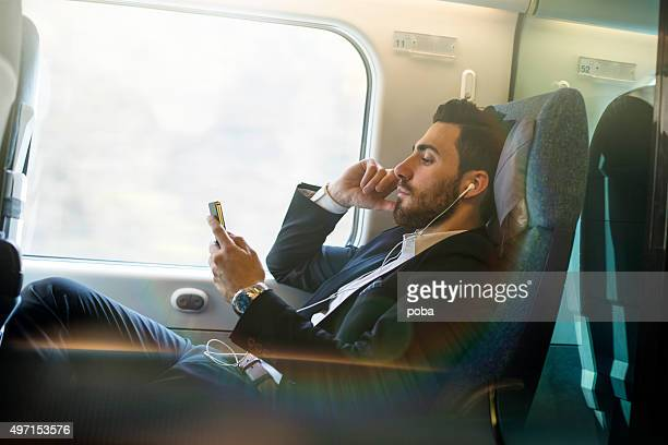 bussinesman seating on a train  beside  window  and using phone