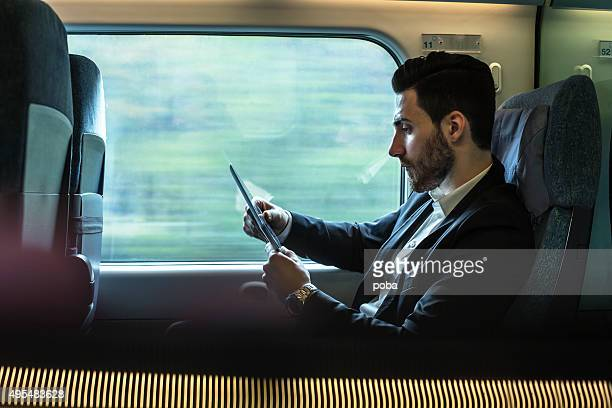 Bussinesman Sitzgelegenheiten auf einen Zug neben Fenster und Arbeiten