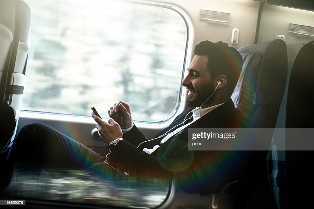 Bussinesman seating on a train beside window and working : Stock Photo