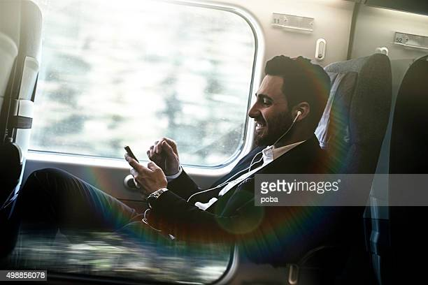 Bussinesman seating on a train beside window and working