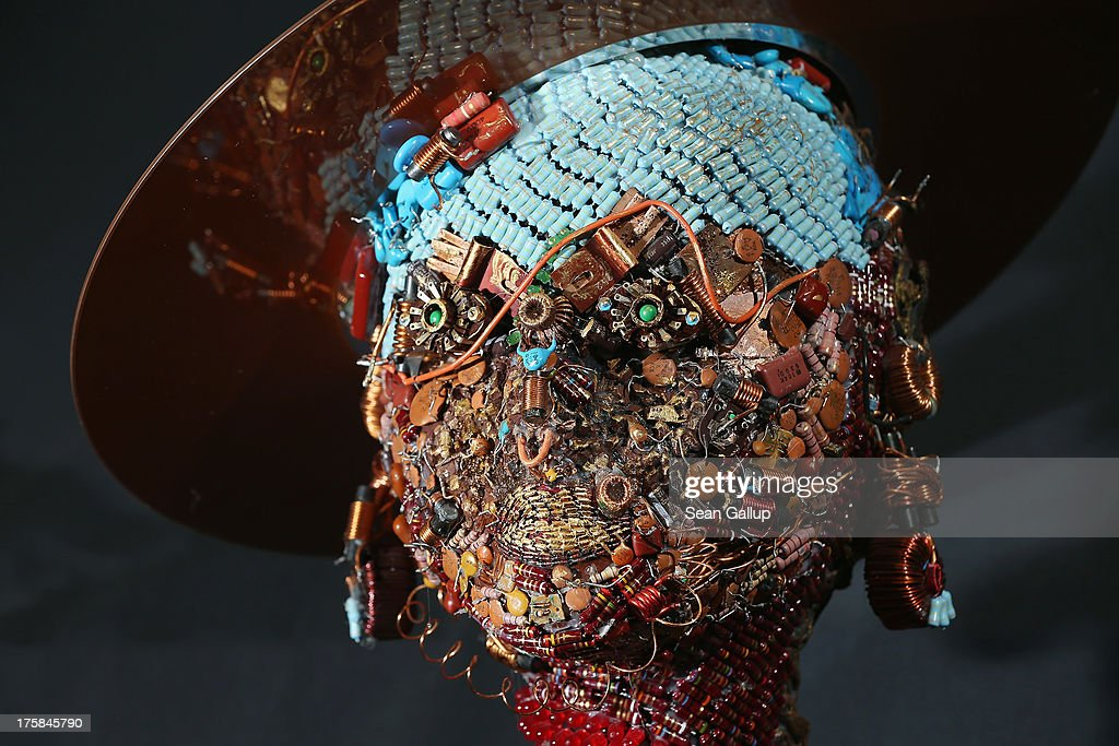 A bust of a female figure wearing a hat and whose surface is completely covered in electronics junk stands at the electronics repair shop owned by Muharrem Batman in Neukoelln disrict on August 8, 2013 in Berlin, Germany. Batman has created a wide variety of busts and even full body sculptures whose outer surfaces are nearly completely covered in electronics capacitors, resistors, bits of circuit boards, CPUs, wiring, keyboards and other scrap he has salvaged from old computers and other devices. Though he says the designs are his own, he admits his sister Ayse and colleague Judith Brun do the much of the actual work. 'I just don't have the patience for it, women can do something like that much better,' he says. He completed his first piece ten years ago, initially solely with the intent of decorating his store, though he has recently launched a website and hopes to have an exhibition.