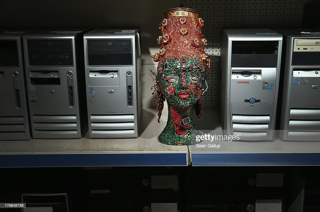 A bust of a female figure with headwear whose surface is completely covered in electronics junk stands among old computers at the electronics repair shop owned by Muharrem Batman in Neukoelln disrict on August 8, 2013 in Berlin, Germany. Batman has created a wide variety of busts and even full body sculptures whose outer surfaces are nearly completely covered in electronics capacitors, resistors, bits of circuit boards, CPUs, wiring, keyboards and other scrap he has salvaged from old computers and other devices. Though he says the designs are his own, he admits his sister Ayse and colleague Judith Brun do the much of the actual work. 'I just don't have the patience for it, women can do something like that much better,' he says. He completed his first piece ten years ago, initially solely with the intent of decorating his store, though he has recently launched a website and hopes to have an exhibition.