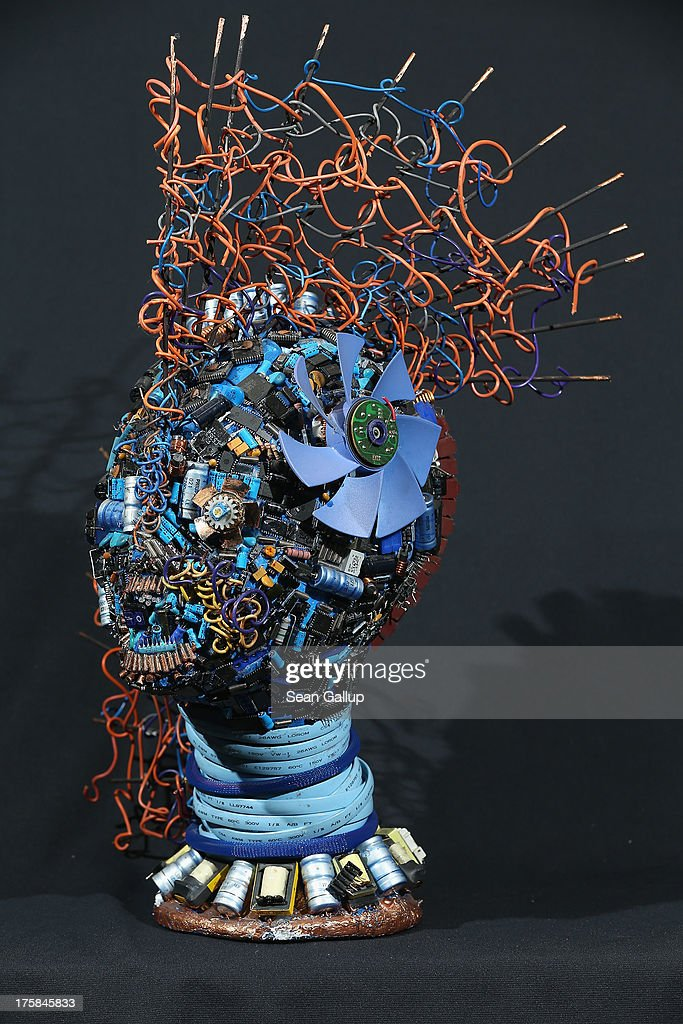 A bust of a male figure whose surface is completely covered in electronics junk stands at the electronics repair shop owned by Muharrem Batman in Neukoelln disrict on August 8, 2013 in Berlin, Germany. Batman has created a wide variety of busts and even full body sculptures whose outer surfaces are nearly completely covered in electronics capacitors, resistors, bits of circuit boards, CPUs, wiring, keyboards and other scrap he has salvaged from old computers and other devices. Though he says the designs are his own, he admits his sister Ayse and colleague Judith Brun do the much of the actual work. 'I just don't have the patience for it, women can do something like that much better,' he says. He completed his first piece ten years ago, initially solely with the intent of decorating his store, though he has recently launched a website and hopes to have an exhibition.
