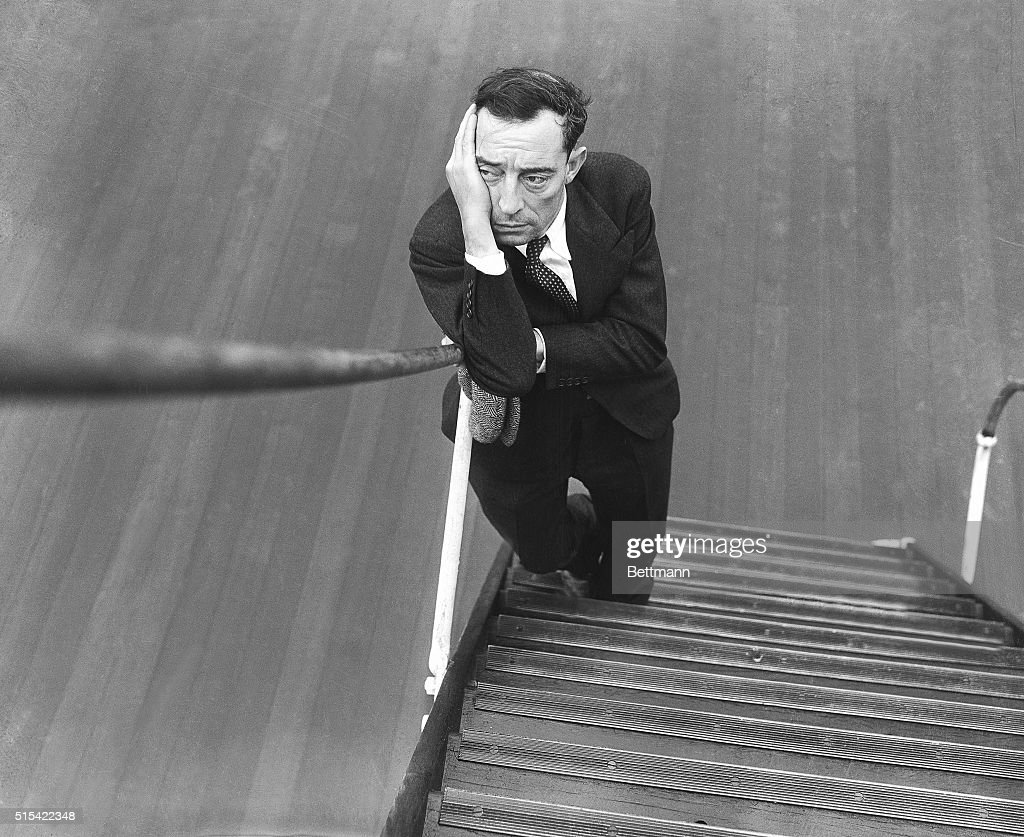 Buster Keaton frowns after being asked by a cameraman to smile at the bottom of the steps of the Isle de France.